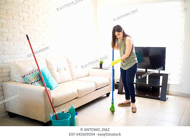 Young maid cleaning house with broom with bucket and disinfectant kept aside near sofa