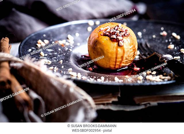 Baked apple with nut- and red jam filling on tin plate