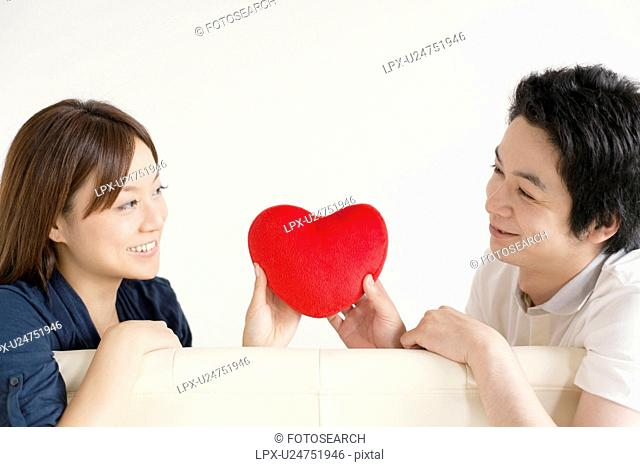 Young couple sitting on sofa holding a heart
