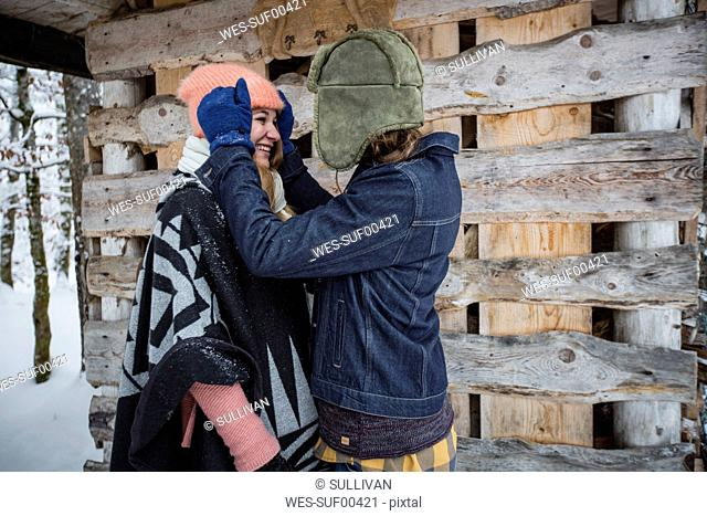 Happy couple in front of wood pile outdoors in winter
