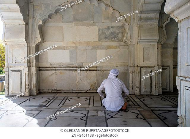 Afghan man in traditional clothes prays in small white marble mosque of Shah Jahan inside the Babur's garden, Kabul, Afghanistan