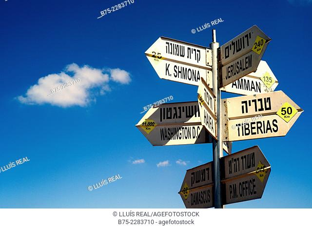 Sign post with a blue sky background pointing out Tiberias, Damascus, Washington, K. Shmona, Jerusalem, Israel in Amman and Haifas