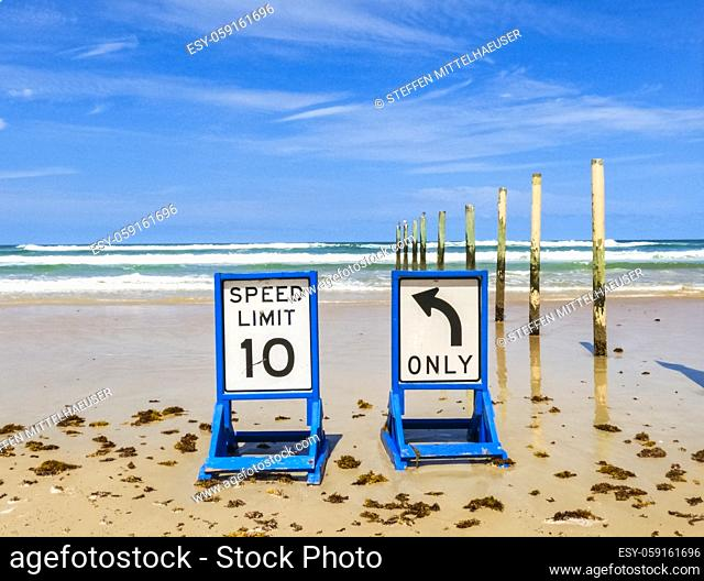 Two beach driving traffic sign sitting on wet sand with Atlantic Ocean waves in the background and seaweed in the forground and whispy cirrus clouds in a bright...
