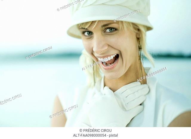 Young woman laughing, gloved hands clasped on chest
