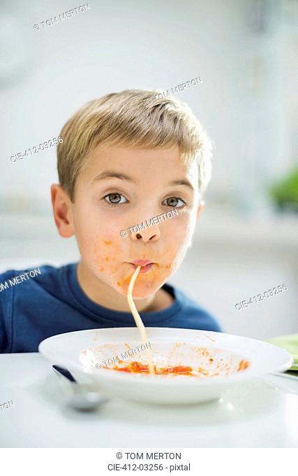 Boy slurping spaghetti at table