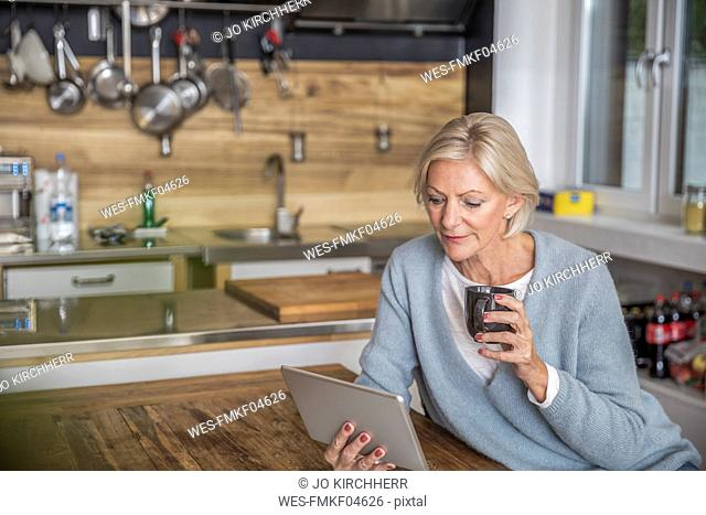 Senior woman using tablet in the kitchen