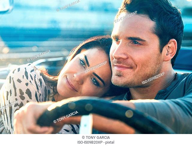 Couple sitting in convertible car, watching sunset