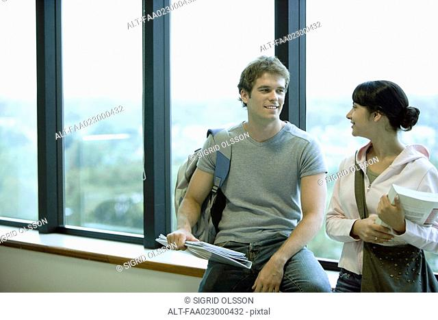Male and female college students, leaning against window, chatting