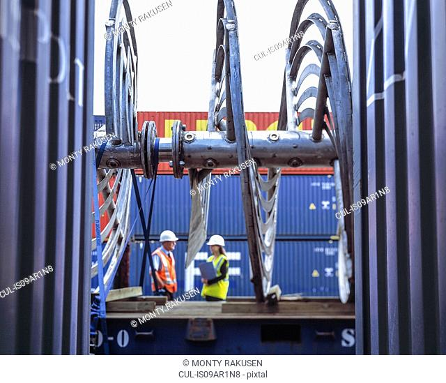 Female and male workers inspecting shipping containers in port, Grimsby, England, United Kingdom