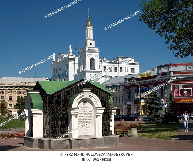 Ukraine Kiev district Podil Kontraktova Place oldest place of town park with spring and memorial with park visitors in background Pirohosci church and belltower...