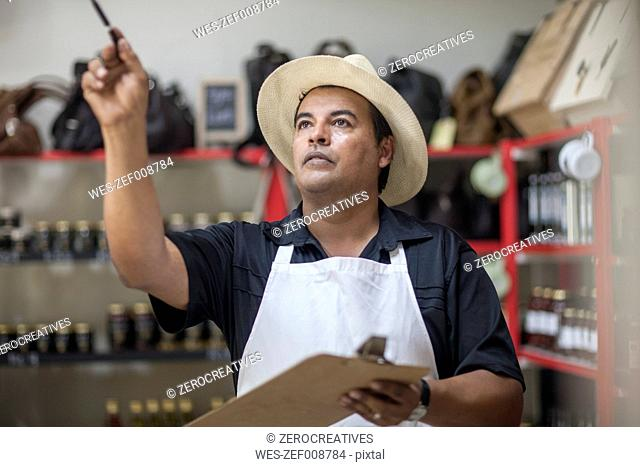 Shopkeeper in shop counting stock