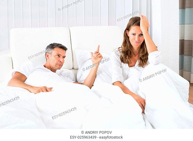 Man Arguing With Depressed Woman Sitting On Bed