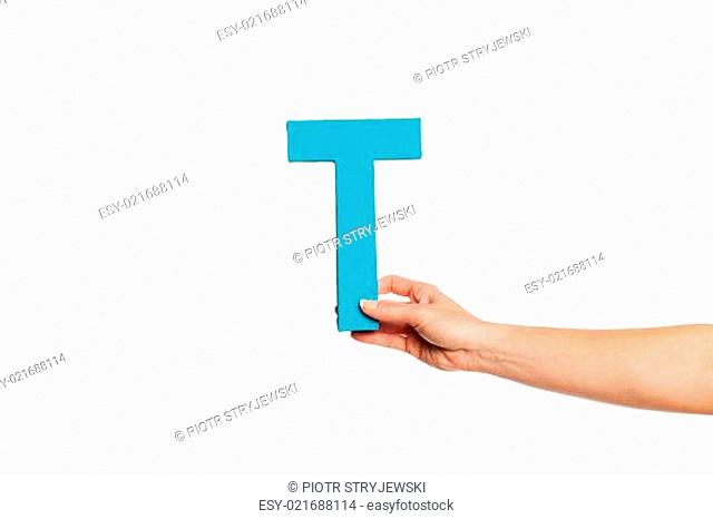 hand holding up the letter T from the right