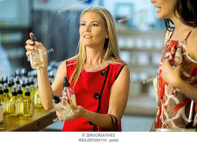 Two women testing scents in shop