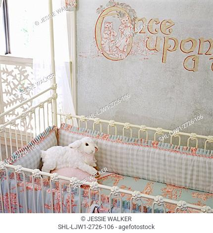 CHILDREN'S ROOM: Detail of crib in nursery, soft blues, tolie sheets with kitten pattern. Mural painted on wall says, 'Once upon a time...'