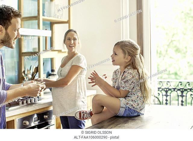 Girl chatting with parents preparing family meal in kitchen