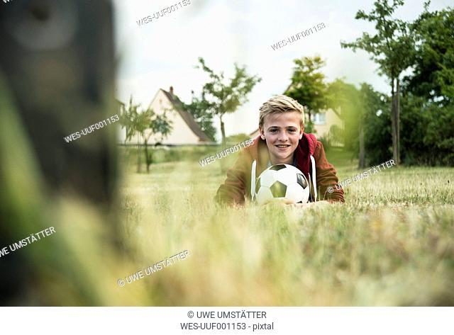 Germany, Mannheim, Teenage boy wizh soccer ball, lying on grass