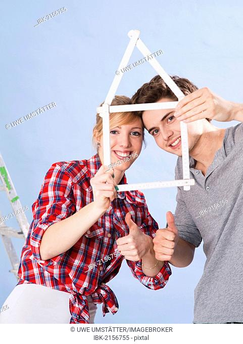 Young couple holding a folding carpenter's ruler in the shape of a house