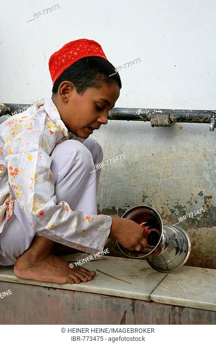Boy cleaning ritual objects used at a shrine, Bareilly, Uttar Pradesh, India, Asia