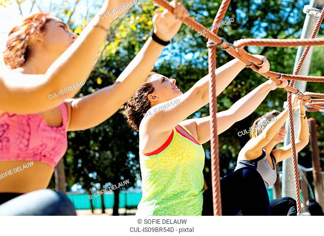 Friends rope climbing in park