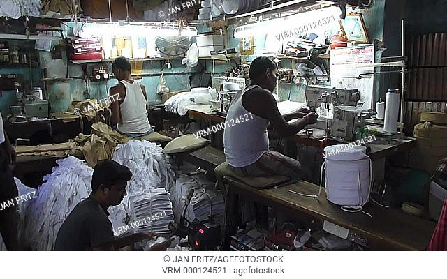 men at work in small and dark workingplace, folding, sewing and packing t-shirts. Calcutta, India