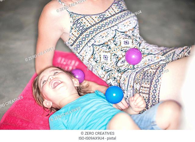 Mother and daughter playing with balls on floor