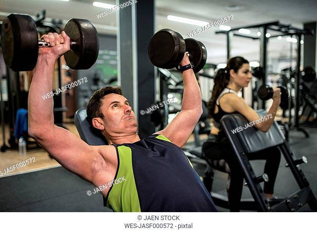 Mature couple training in gym, man doing pectoral muscle exercises and woman biceps exercises
