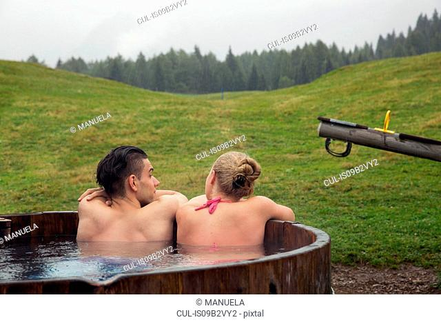 Rear view of young couple relaxing in rural hot tub, Sattelbergalm, Tyrol, Austria