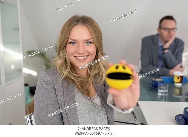 Smiling woman holding smiley face in conference room