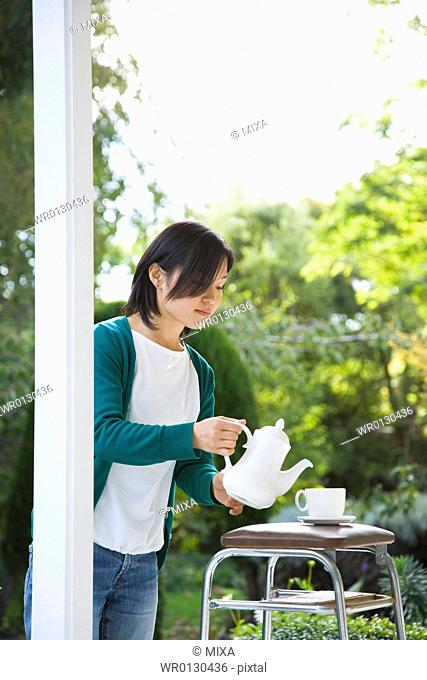 Young woman pouring tea