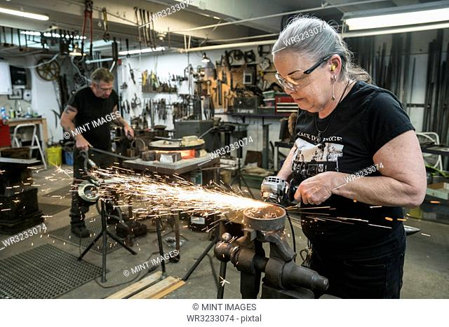 Caucasian female blacksmith grinding on a metal part in her studio. Male blacksmith at work in the background