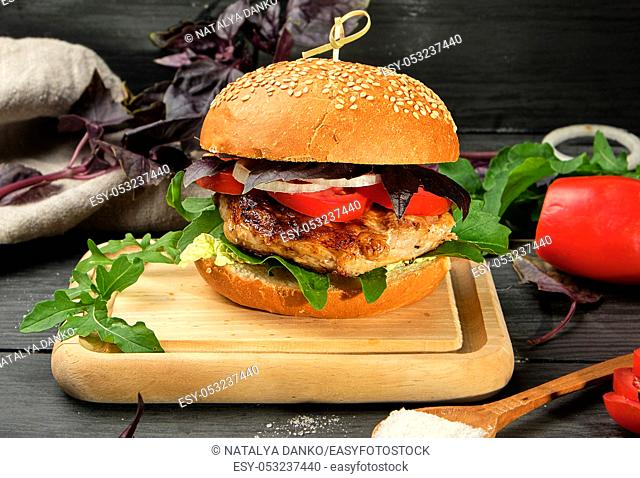 homemade hamburger with pork fried steak, red tomatoes, fresh round bun with sesame seeds on wooden board, close up
