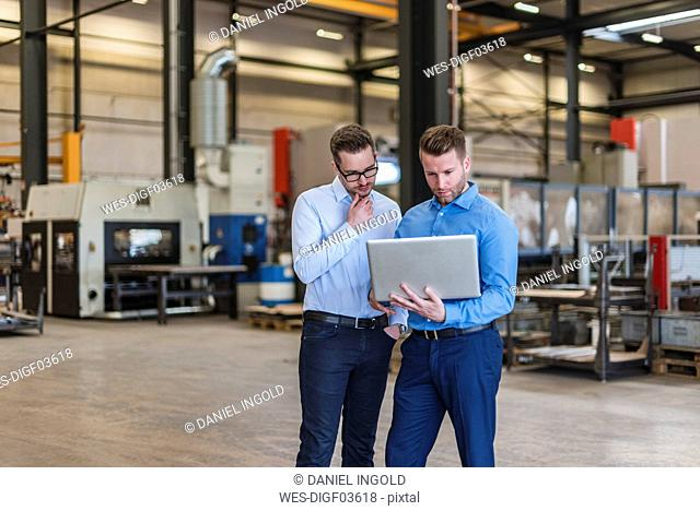Two businessmen sharing laptop on factory shop floor
