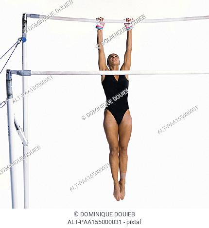 Young female gymnast hanging on uneven bars