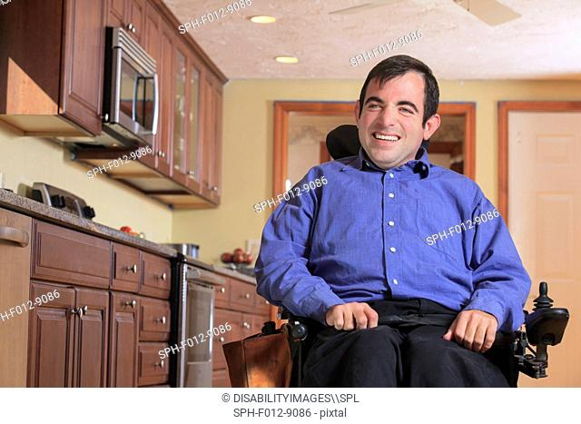 Man with Cerebral Palsy in his motorized wheelchair in his kitchen