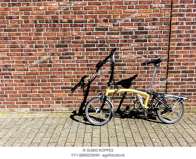 Tilburg, Netherlands. Brompton folding bike parked against a brick wall on a sunny, summer day