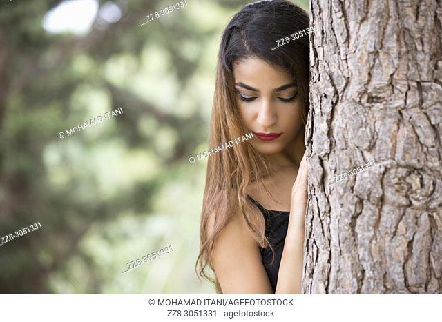 Sad young woman hiding behind a tree