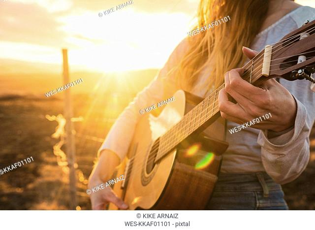 Iceland, woman playing guitar at sunset