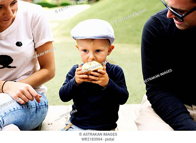 Parents watching son eating bread in park