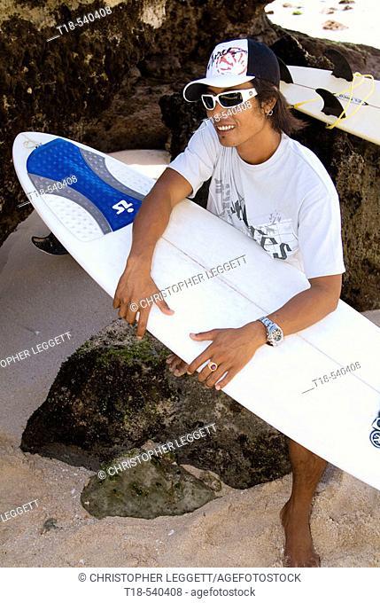 surfer sitting on rock holding surfboard
