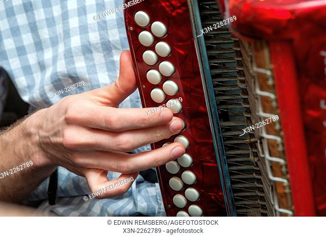 Close-up of a hand pushing accordion buttons in Baltimore, MD