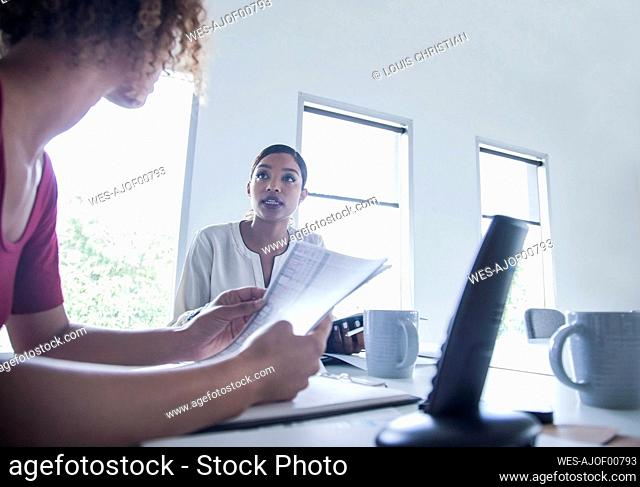 Female entrepreneur with paper standing by colleague at office