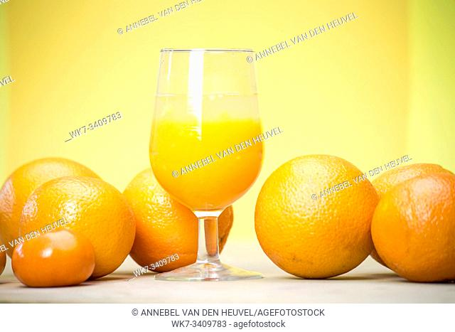 glass of fresh orange juice with fresh fruits on wooden table healthy concept
