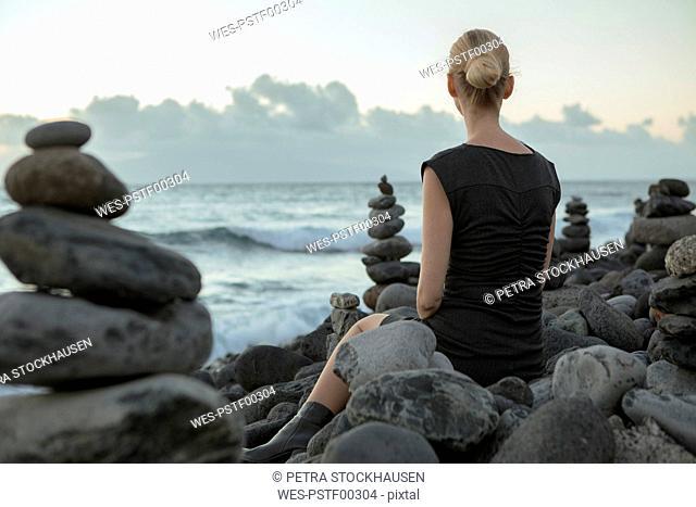 Spain, Tenerife, Costa Adeje, woman sitting between cairns at the coast