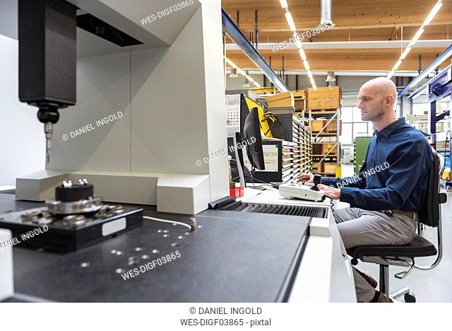 Man using computer at machine in modern factory
