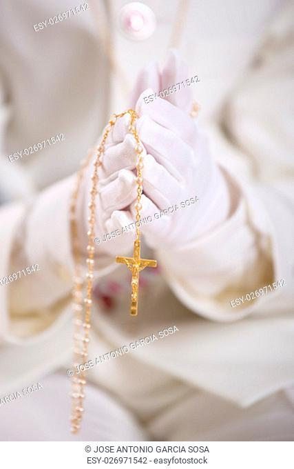 Closeup of a boy's hands with white gloves holding a gold rosary for his First Holy Communion. Shallow depth of field