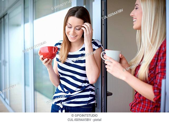 Two female friends, drinking coffee, outdoors