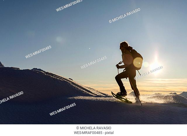 Woman walking with snowshoes in fresh snow in the mountains at sunset, Valmalenco, Italy