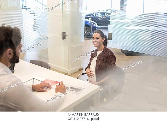 Car salesman talking to pregnant customer in car dealership office