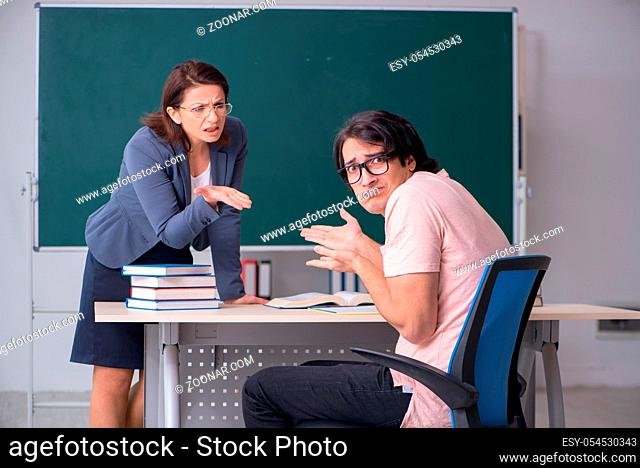 The old female teacher and male student in the classroom